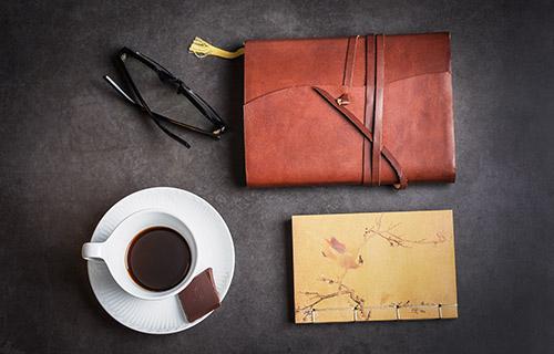 Kaffe, briller, notesbog og taske